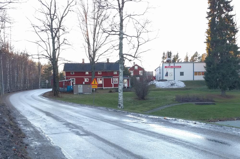 """Nutida bild (2016) på samma plats utefter vägen """"Kalvstigen"""" till Järvsö """" Carl Rudolphis gård låg framför det röda huset, där det nu är en gräsplätt och en damm (privat)."""