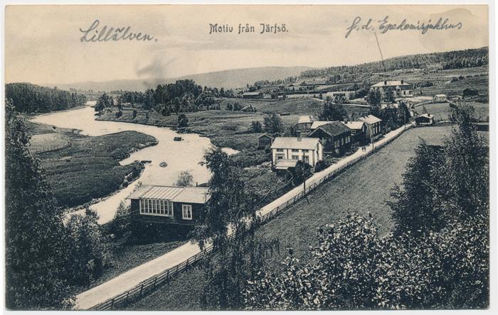 """Vykort """"Motiv från Järvsö"""", 1915, byggnaden med ateljén syns till vänster efter vägen (V038)."""
