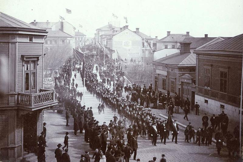 Demonstration i Hudiksvall för 8-timmars arbetsdag och allmän rösträtt 1899, foto: Gustaf Hallin. Silverbild på kartong något beskuren, 204 x 150 mm, Hälsinglands museum.